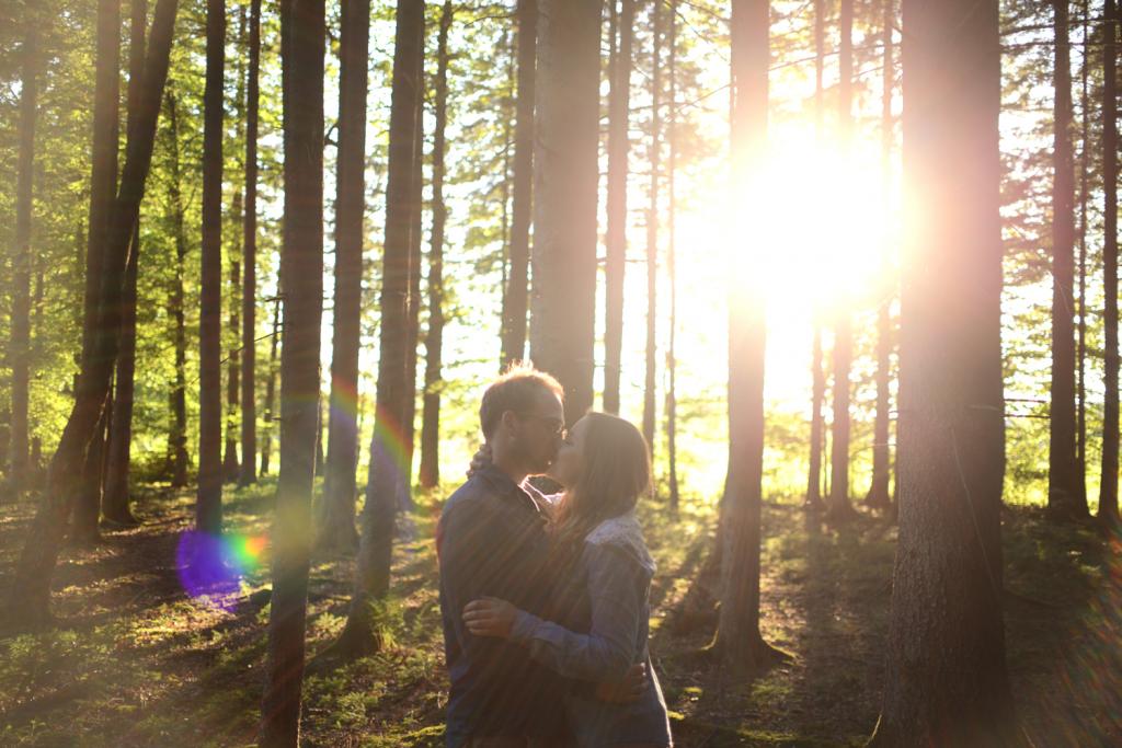 Verliebtes Pärchen küsst sich im Sonnenuntergang im Wald Couple Shooting
